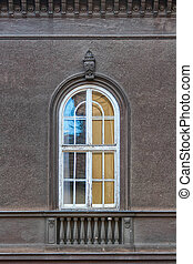 Old arched window, with weathered wooden frame