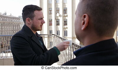 Two young businesspeople talking on the balcony in a restaurant