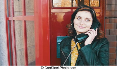 Happy Girl in a Red Telephone Booth Talking on the Phone in...