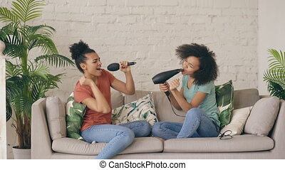 Mixed race young funny girls dance singing with hairdryer and comb sitting on sofa. Sisters having fun leisure in living room at home concept