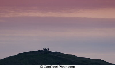 Group Of People On Hilltop At Sunset - Group of people on...