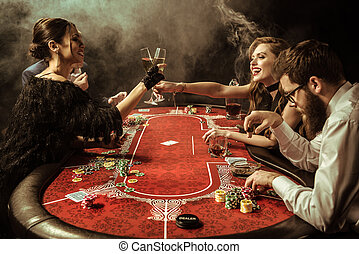 side view of women clinking drinks while playing poker in...