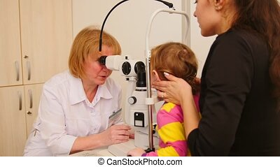 Little child at ophthalmology's doctor - optometrist checks...