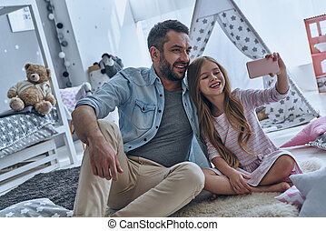 Selfie time! Cheerful father and his little daughter taking...