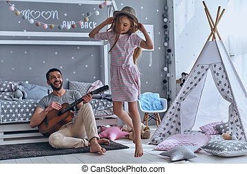 Carefree time together. Cheerful father playing guitar for...