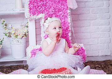 Little girl on her birthday eating cake