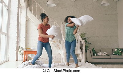 Slow motion of two mixed race young pretty girls jumping on bed and fight pillows having fun at home