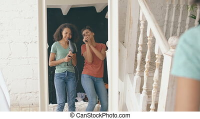 Mixed race young funny girls dance singing with hairdryer and comb in front of mirror. Sisters having fun leisure in bedroom at home concept