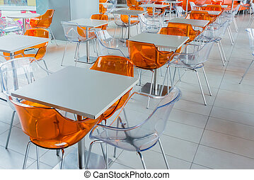 Orange plastic chairs and a white table on food court in business shopping center, modern interior design.