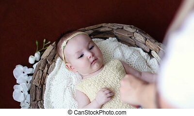 baby is lying in bed on the back in yellow knit clothes and...