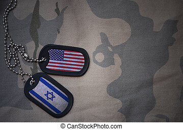 army blank, dog tag with flag of united states of america and israel on the khaki texture background. military concept