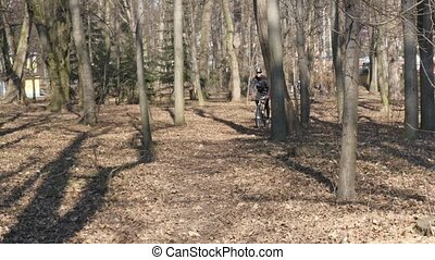 the path scattered with autumnal leaves, man passing by on the bike