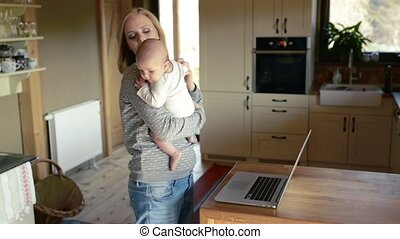 Beautiful young mother with son in the arms, working on...