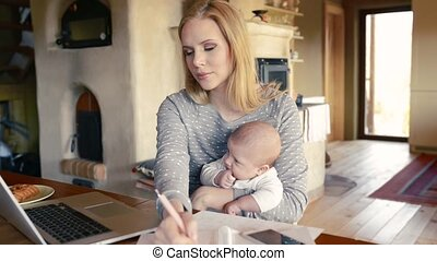 Beautiful mother with son in the arms, working on laptop