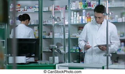 Pharmacists checking medicines at pharmacy - Two phermacists...