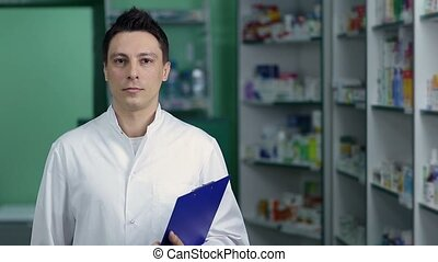 Smiling male pharmacist in white coat at drugstore -...