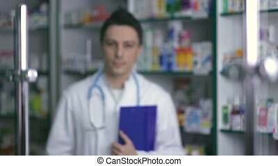 Smiling male pharmacist in white coat in drugstore