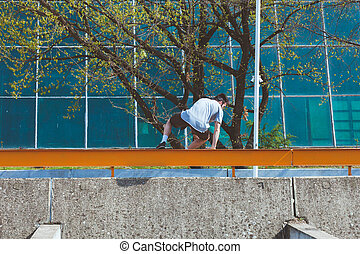 young man doing parkour in the city - young man doing...