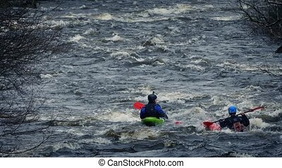 Kayaks On River Rapids - People in kayaks on wild river