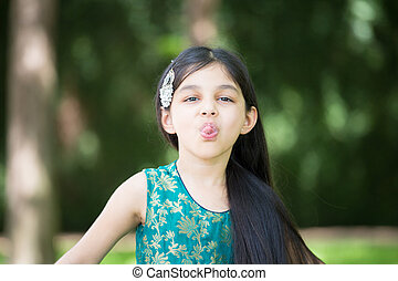 Tongue out - Closeup portrait, young girl sticking tongue...