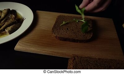 The chef makes a sandwich with sprats - Chef cook in a black...