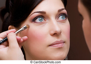 make up artist makeing a colour correction with an brush to...