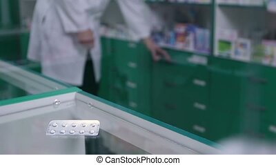 Close-up of pills in blister pack lying on counter -...