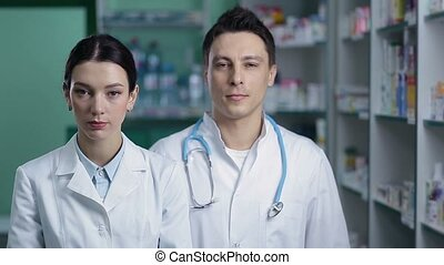 Smiling friendly pharmacists working in pharmacy - Portrait...