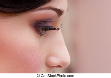 profile closeup of beautiful brunette young lady with make up