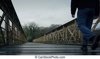 Man Walks On Old Train Bridge - Man walking across old train...
