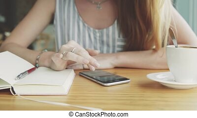 Woman working on smartphone in cafe with cup of coffee and notebook on the table.
