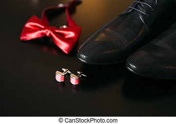 Black shoes of the groom, red bow tie, cufflinks, belt, on a bla