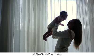 mother and young daughter standing at the window