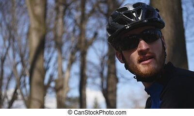 Close up shot of professional rider wears cycling clothing, protective helmet and glasses