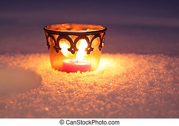 Burning candle in the snow