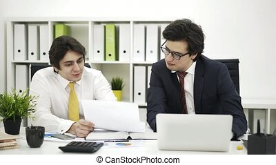 Two coworkers discuss business - Two businessmen are sitting...