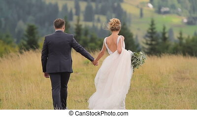 Wedding Couple Walks in Mountains