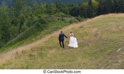 Wedding Couple Walks near Mountain Canyon