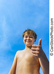 happy smiling young boy at the beach gives thumbs up sign...