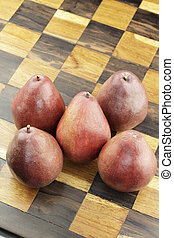 Red Pears on a Wooden Chess Board