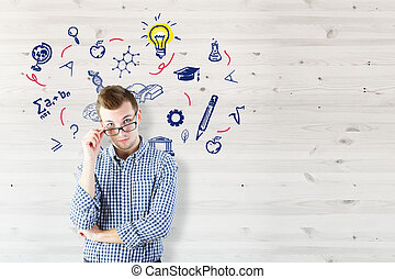 Science concept - Portrait of thoughtful young man on wooden...
