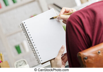 Female holding and writing in spiral notepad - Close up of...
