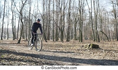 cyclist standing on front wheel in the park. Autumn leaves on the ground slow motion