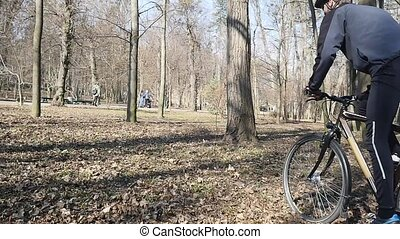 cyclist rides in the park. Autumn leaves on the ground