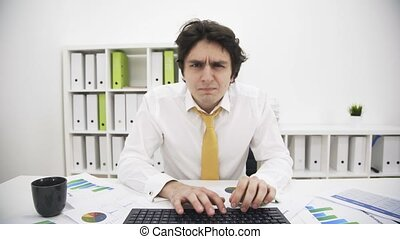 Front view of typing stressed man - Front view of a stressed...