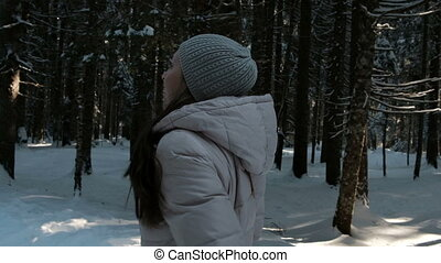 Beautiful brunette walks on snow covered coniferous forest....