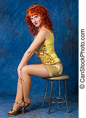 Beautiful young red-haired girl in a yellow dress