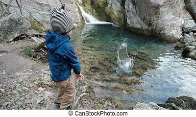 Charming boy plays near beautiful cascade. Cute child throws...