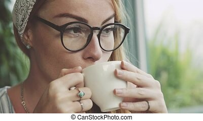 Beautiful young woman drinking coffee in cosy cafe. Girl...