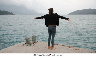 Woman stand on pier, raise her hand. View from back. Camera...